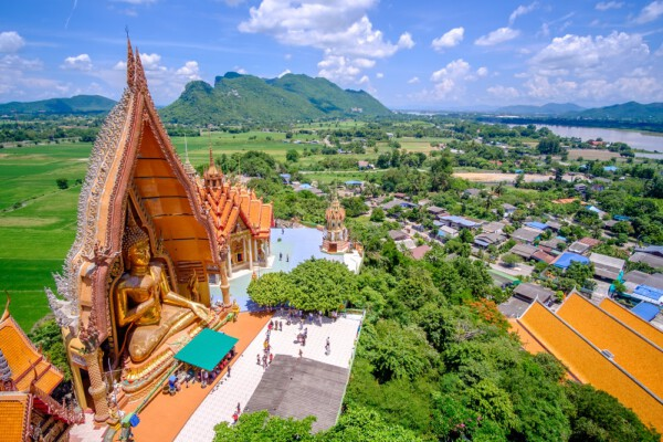 Aerial view of Tiger Cave Temple ( Wat Tham Suea) with the green rice field and blue sky background at Kanchanaburi province, Thailand