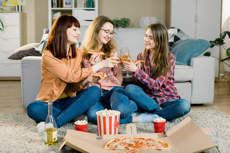 Three beautiful young women drinking wine and eating pizza at home. Happy Beautiful Friends Laughing, Eating Pizza At Home Party. Woman Having Dinner Together, Enjoying Meal. Leisure, Friendship.