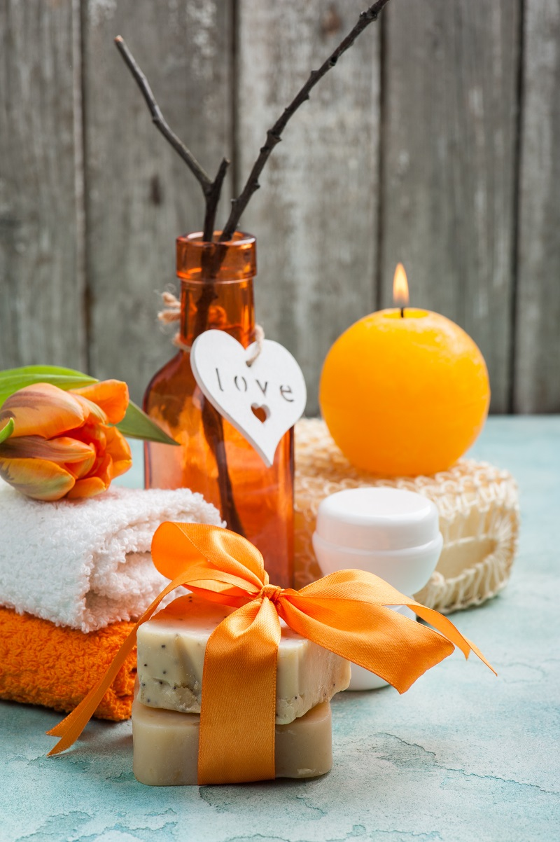 Spa composition with handmade organic soap and orange bow. Cosmetics on blue concrete table close-up