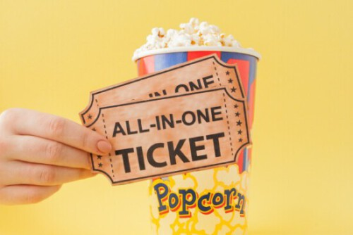 Hand takes a movie tickets and popcorn from a paper cup on a yellow background. Woman eats popcorn. Cinema Concept. Flat lay. Copy space.