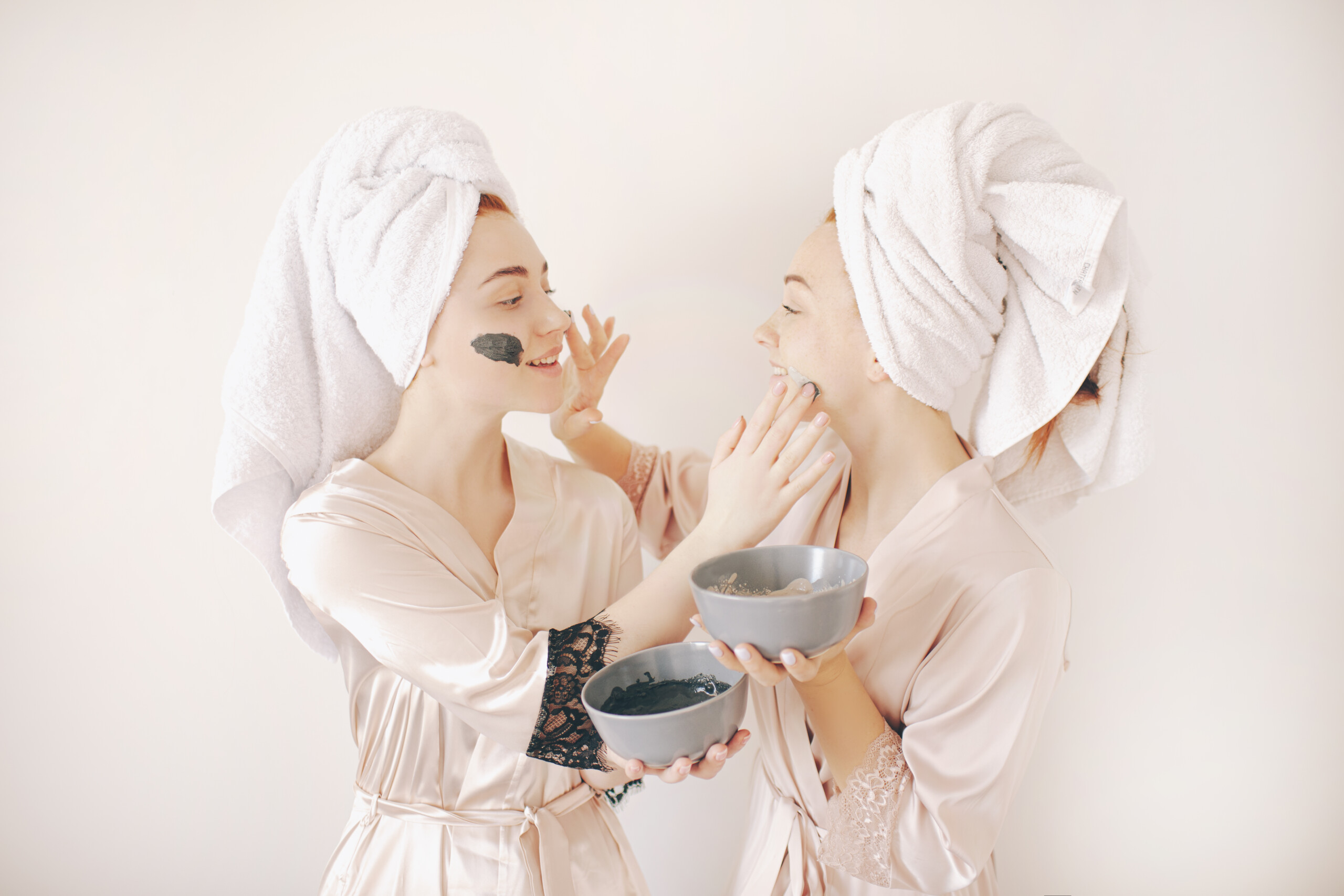 Two young women sisters in bathrobes with towels on their heads isolated on a white background. Spa at home. They make a mask for skin care on the face. And applied to the skin of the face.